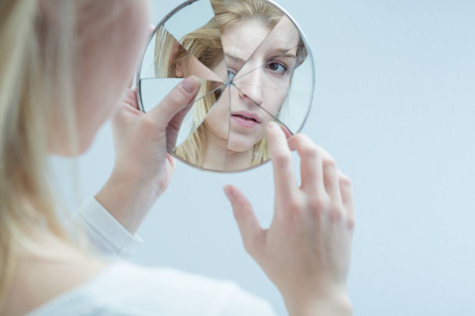 Young woman touching her own reflection in a broken mirror