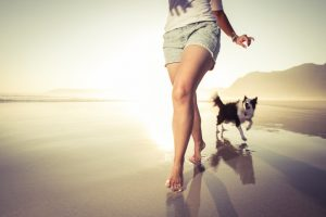 Torso and legs of teenager running along beach with dog