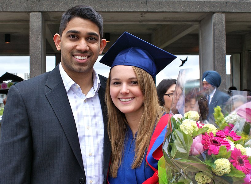 A photo of a young couple, the woman (Lauren Ufford) is wearing a blue cap and gown and holding flowers and the man standing with her is wearing a suit and they are both smiling at the camera