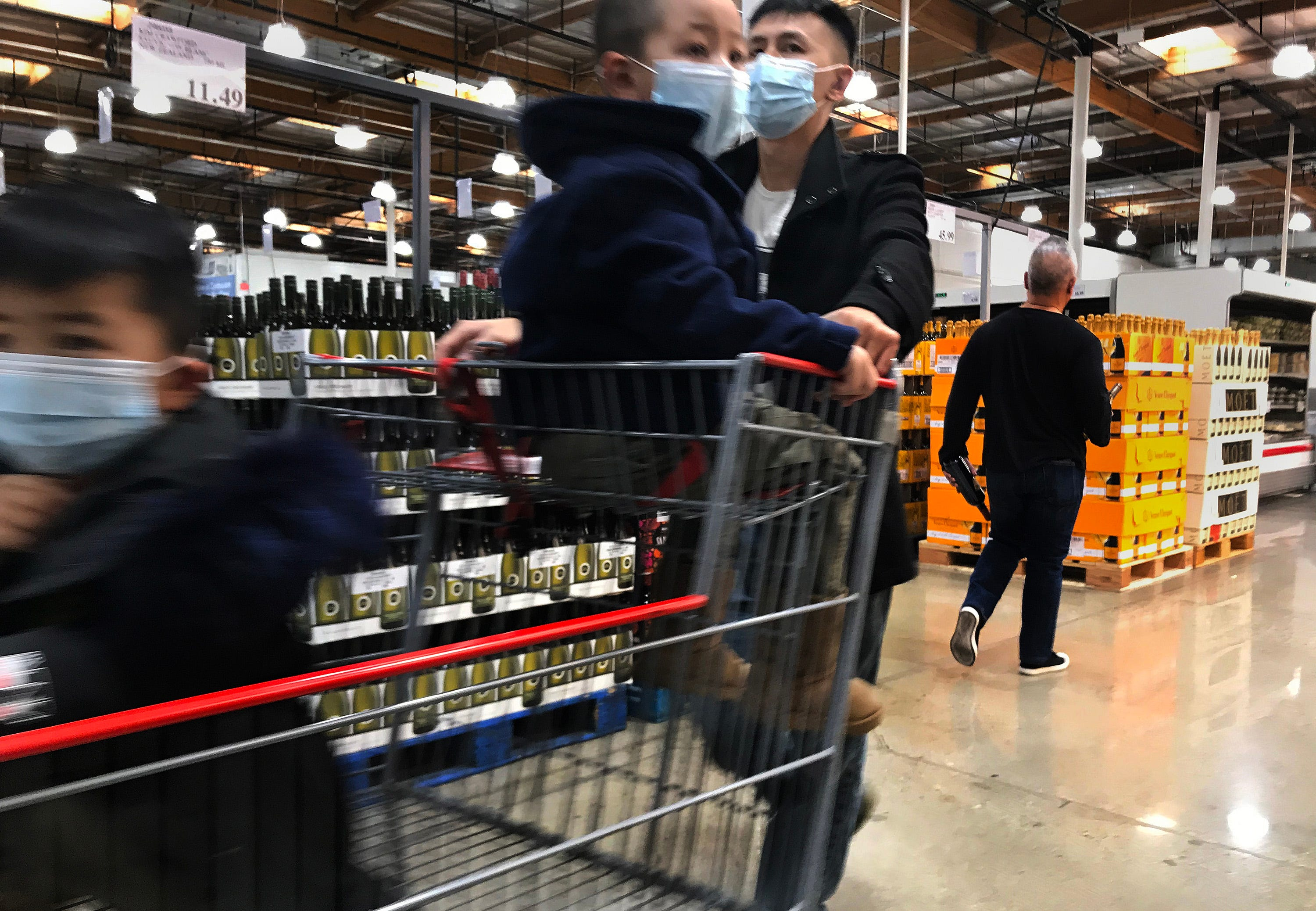 A shopper with his young children all wear masks to protect against coronavirus while shopping at Costco on March 7, 2020 in Alhambra, Calif.