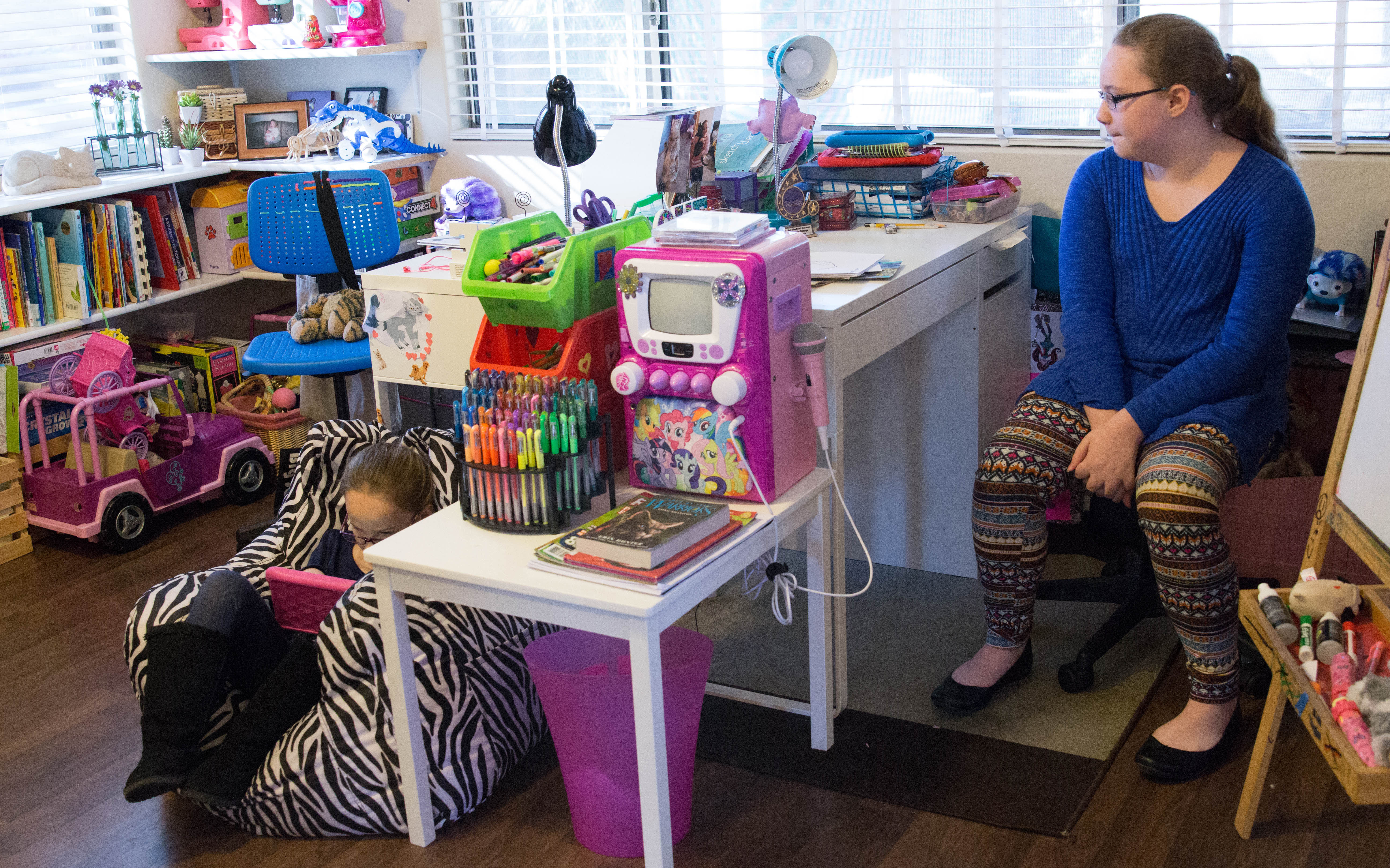 Cora Childress (left) and Caitlin Childress use Buzzies. Their mother said they both have anxiety.(Photo by Megan Bridgeman/ Cronkite News)