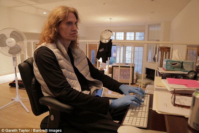 Stephen Forde wearing latex gloves to type at home. He admits to washing his hands up to 75 times a day