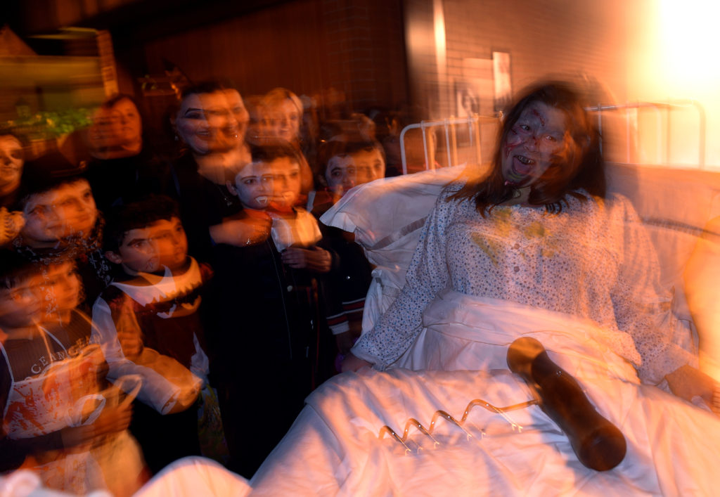 A woman dressed up as a character from the movie The Exorcist reacts during Halloween in La Fresneda