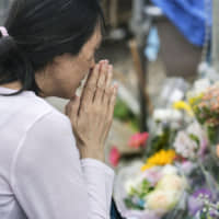A woman prays at the site of a mass stabbing on June 4, a week after the incident in which a knife-wielding man killed two and injured more than 15 people near a bus stop in Kawasaki.