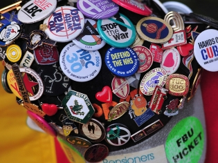 A cap bearing left-wing campaign badges.