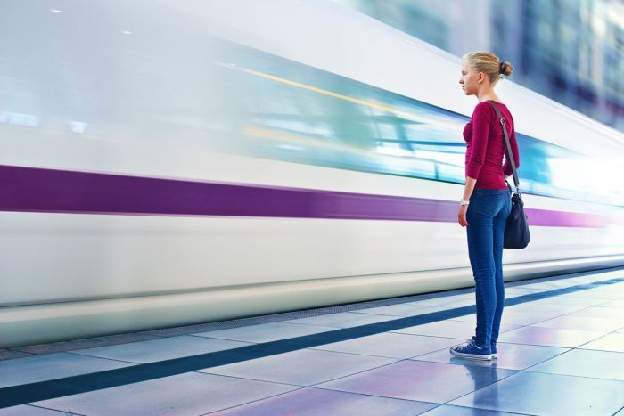 A girl standing close the a fast passing train