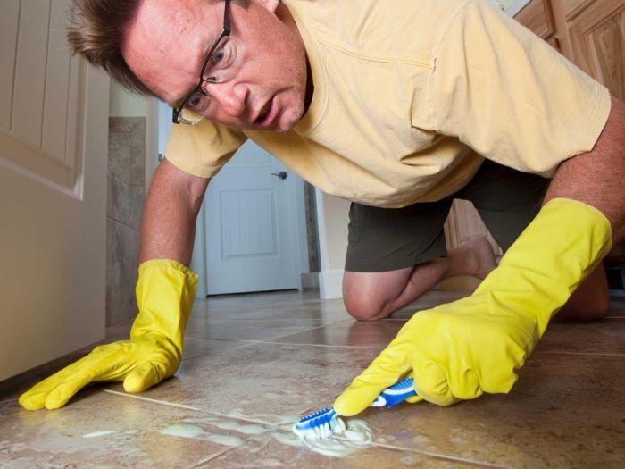 A man scrubbing the floor tiles