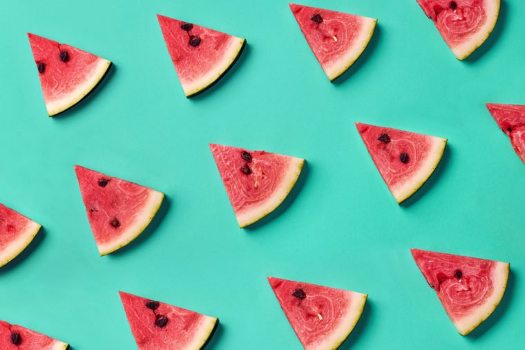 Colorful fruit pattern of fresh watermelon slices on blue background. From top view