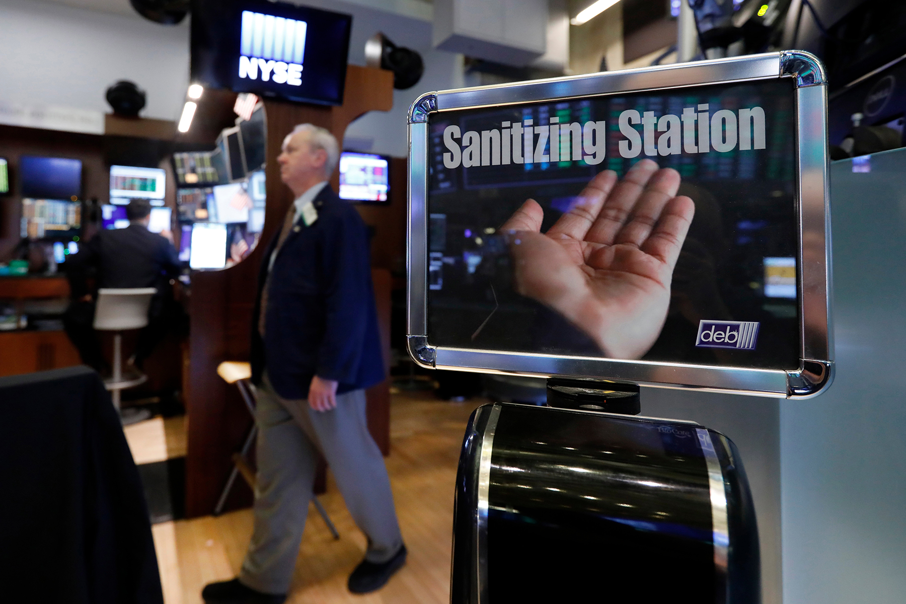 A trader passes a hand sanitizing station on the floor of the New York Stock Exchange, . Federal Reserve Chairman Jerome Powell noted that the coronavirus poses evolving risks to economic activityVirus Outbreak Economy, New York, USA - 03 Mar 2020